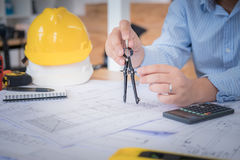 Architect or planner working on drawings for construction. Plans at a table stock images
