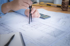 Architect or planner working on drawings for construction. Plans at a table stock photography