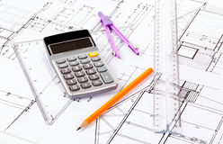 Architect plans. Desk of an architect with plan, pencil, circle and pocket calculator Royalty Free Stock Photo