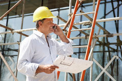 Architect With Plans Outside. New Home Talking On Mobile Phone Royalty Free Stock Images
