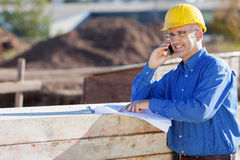 Architect Pointing At Blueprint While Using Mobile Phone At Site Stock Photo