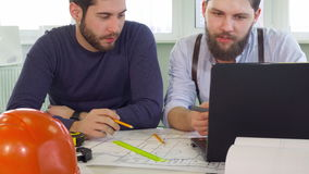 Architect points his pencil on laptop screen. Young male architect pointing his pencil at the laptop screen at the office. Brunette bearded construction engineer