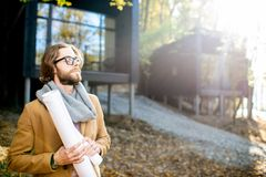 Architect portrait outdoors. Portrait of a handsome man architect standing with drawings in front of the modern houses in the forest royalty free stock image