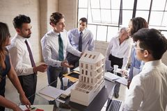 Architect presenting a design model to business colleagues royalty free stock photos