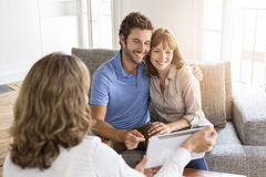 Architect presenting a new project  on digital tablet to a couple. Consultant showing informations about new property on tablet PC to future owners Royalty Free Stock Photography