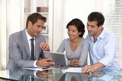 Architect presenting a new project to a smiling young couple Royalty Free Stock Images