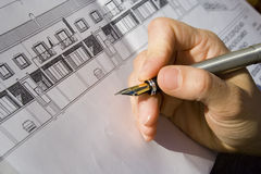 Architect project. A hand signing the architecture project of a house Royalty Free Stock Image