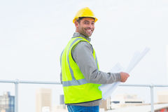Architect in protective clothing holding blueprint outdoors Royalty Free Stock Photography
