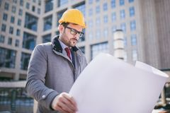 Architect in protective helmet holding blueprint. In front of office building Stock Image