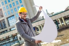 Architect in protective helmet holding blueprint. In front of office building Royalty Free Stock Image