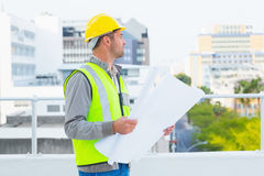 Architect in protective workwear holding blueprints outdoors Royalty Free Stock Image