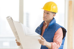 Architect Reading Blueprint At Construction Site Stock Photo