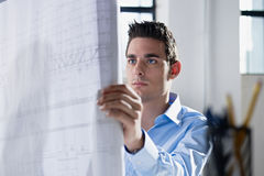 Architect reading blueprint in office Royalty Free Stock Photography