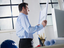 Architect reading blueprint in office Stock Photos