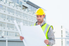 Architect reading blueprint outside building Royalty Free Stock Images