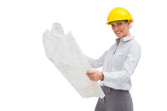 Architect reading blueprint with yellow helmet Stock Photography