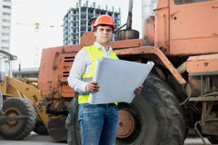 Architect reading blueprints next to bulldozer at building site Stock Images