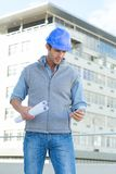 Architect reading text message thought mobile phone. Male architect with blueprints reading text message thought mobile phone outside building Stock Image