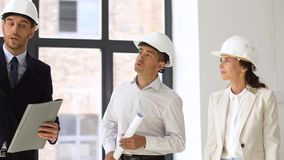 Architect or realtor showing office to customers. Architecture, construction business and people concept - architect or realtor showing new office room to stock video