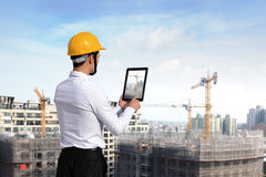 Architect. Rear view of architect looking tablet pc and comparing housing project with building Royalty Free Stock Photography