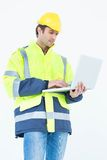 Architect in reflective clothing using laptop computer Stock Photo
