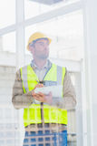 Architect in reflective clothing writing on clipboard at office Stock Photos