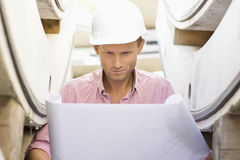 Architect reviewing blueprint at construction site Stock Image