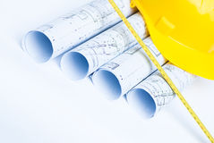 Architect rolls and plansand yellow helmet Stock Images