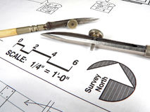 Architect's Tools and Plans. A closeup of an architect's desktop with various tools of the trade, blueprints, and design drawings Stock Photo