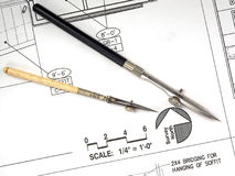 Architect's Tools and Plans. A closeup of an architect's desktop with various tools of the trade, blueprints, and design drawings Royalty Free Stock Image