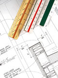 Architect's Tools and Plans. A closeup of an architect's desktop with various tools of the trade, blueprints, and design drawings Royalty Free Stock Photo