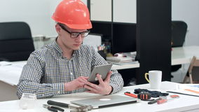 Architect with safety helmet using electronic tablet in the office stock video