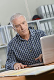 Architect sat working at desk Stock Images