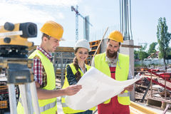 Architect sharing ideas about plan of building project on construction site Stock Photos