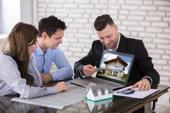 Architect Showing House Model To Couple In Office Royalty Free Stock Photography