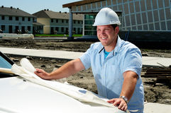 Architect On Site. Young Handsome Male Construction Site Foreman, Checking The Blueprints Royalty Free Stock Photo