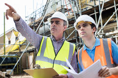 Architect On Site Discussing Plans With Builder Royalty Free Stock Photography