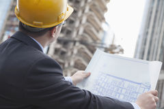 Architect on site looking at blueprints Royalty Free Stock Photo