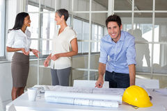 Architect smiles at camera while coworkers stand in background Stock Images