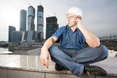 The architect speaking over mobile phone. The architect wearing a protective helmet sitting in front of a building site and speaking over mobile phone Stock Photo