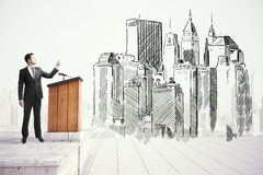 Architect speaking in public. Young architect giving public speech next to abstarct construction sketch on white background stock photography