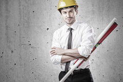 Architect with spirit level and plan. At site Royalty Free Stock Photography