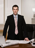 Architect standing with blueprints at desk Royalty Free Stock Photos