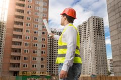 Male architect standing on building site and pointing on buildings under construction with blueprints. Architect standing on building site and pointing on stock photos