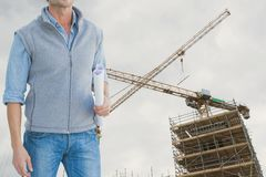 Architect standing on holds plan against building under construction background. Digital composite of construction torso Royalty Free Stock Photography