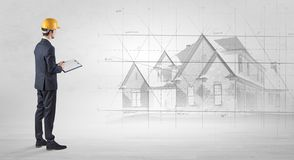 Architect standing with house plan. Architect standing and watching an imagined house plan stock photo