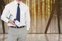 Architect standing on with one hand in the pocket and the other holding plan against indoors backgro Stock Photography