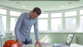 Architect stands near the desk at the office. Handsome male architect standing near the desk at the office. Young construction engineer bending over the table