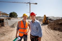 Architect and structural engineer dressed in orange work vests and helmets stand on the open air building site royalty free stock image