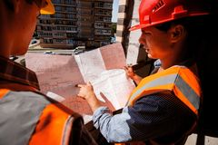 Architect and structural engineer dressed in shirts, orange work vests and helmets explore construction documentation on stock images